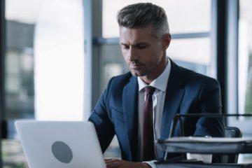 Homme en costume devant son ordinateur